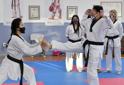Cynthia Haskins of Edgewood, center, breaks a board held by Master Youngshin Jennifer Chang under the watchful eye of Grand Master Se Young Chang, back, and friends Puja Tayloe and Terri Schurr during a class session at the U.S. Taekwondo Academy in Bel AIr. Haskins has studied at the academy for seven years and has become a third degree Black Belt in Taekwondo.