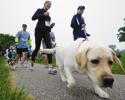 From left, Charles Sauerwein, Amanda Wilbarn, and Cassie Chance leave the starting line during the 5K-9 Mutt Run in Mount Airy May 14, 2011.