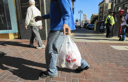 A Baltimore City Council committee on Monday advanced a proposal to ban retailers from giving shoppers plastic bags in most cases and requiring them to charge a nickel for any other type of bag, including paper. A shopper carrying a plastic bag is shown in this file photo.