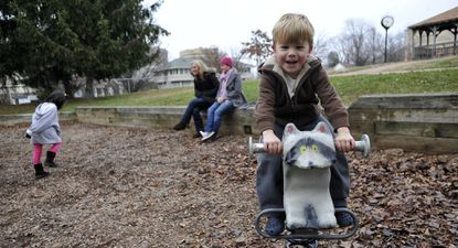 Charlie Sanders, 5, rides a raccoon as he plays in Towson Manor Park.