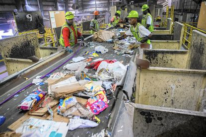 Workers remove plastic bags during sorting at the Waste Management's CID Recycling Center on the Chicago's South Side.