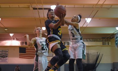 St. Frances Panthers guard Tyeisha Smith (3) drives to the paint for a basket, between Seton Keough Gators' Sydney Mitchell (left) and Kayla Bacon.