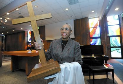 Lillian Dove removes the cross after the Baptist worship at the Oakland Mills Interfaith Center which serves many denominations.