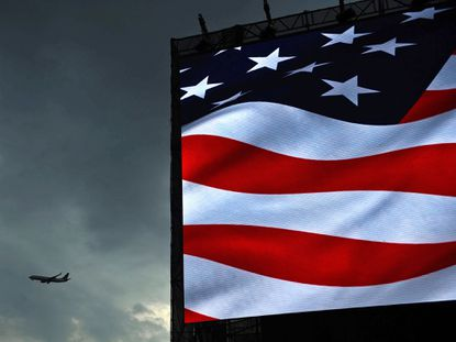 A plane flies through cloudy skies past a screen on the National Mall showing the American flag.