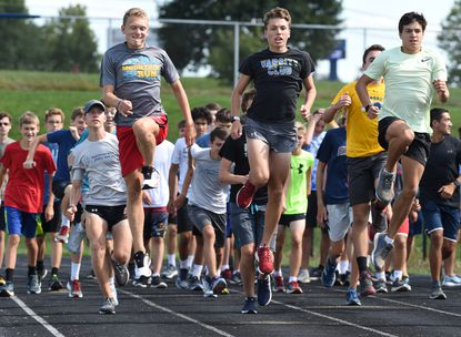 Liberty High runners, from left, Woodrow Kashima, Jake Beaumier and Connor Stewart lead fellow cross country teammates in warm-ups during a practice at the school on Thursday, August 29.