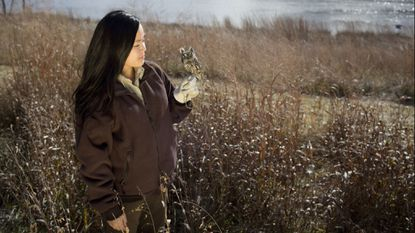 U.S Fish and Wildlife Service's Jennifer Chin poses for a photo with a 4-year-old Eastern screech owl outside the National Wildlife Visitor Center at the Patuxent Research Refuge in Laurel last December