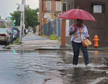 A pedestrian walks through the water while crossing Aliceanna Street, getting her feet wet from the aftermath of a severe downpour that resulted in flash flooding in Fells Point.
