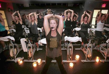 Instructor Janet Fitzgerald leads a class at SoulCycle, an indoor cycling studio based in New York. Arm weights are part of the class.