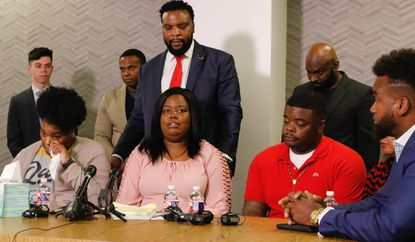 Amber Carr, left, wipes a tear as her sister Ashley Carr, center, talks about their sister, Atatiana Jefferson, as their brother, Adarius Carr, right and attorney Lee Merritt, standing, listen during a news conference on Oct. 14, 2019 in downtown Dallas.