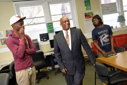 """Christopher Eames,24, (left), and Natheno Frazier-Bey, 25, (right) listen as City Council President Bernard C. """"Jack"""" Young (middle) talks with them at the Youth Empowered Society Drop-In Center."""