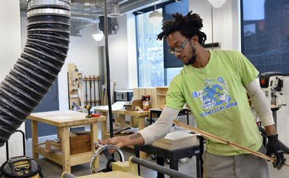 Chris Priest of Baltimore uses a planer to smoothe a wooden board. He does woodworking at Open Works worker space on Greenmount Avenue.