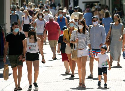 People wearing face masks to protect against coronavirus, walk down a street, in Saint Jean de Luz, southwestern France, Wednesday, Aug. 5, 2020. Since Monday, 69 towns in western France imposed outdoor mask rules to slow the spread of coronavirus.