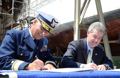 """Coast Guard Rear Admiral Ronald J. Rabago, left, and Shawn Garvin of the U.S. Environmental Protection Agency sign paperwork signifying that environmental cleanup is complete at the Coast Guard Yard in Curtis Bay. Now that cleanup is complete, the yard can be removed from the """"Superfund"""" or National Priorities List of contaminated sites. Parts of the yard were contaminated by past shipbuilding and ship repair activities."""
