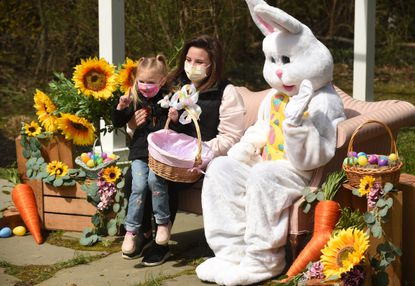 Three-year-old Emeline Ewing sits on the lap of her mother, Lindsey Ewing of Westminster, as they pose with the Easter Bunnyt, during an Easter egg hunt at Seasons at Magnolia Manor on Saturday, April 3, 2021. Families preregistered for the free event, which included three egg fields, a mobile petting zoo and the Easter Bunny.