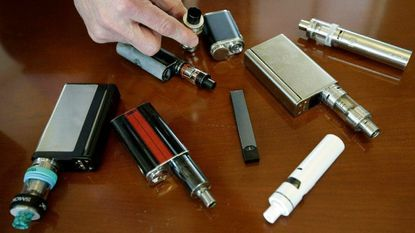 A Massachusetts high school principal displays vaping devices April 10, 2018, that were confiscated from students. On April 3, 2019, the Food and Drug Administration said it has not established a direct connection between vaping and seizures but seeks more information.