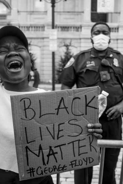 """""""A protestor chanting """"Black Lives Matter"""" during a peaceful protest at City Hall in Baltimore."""