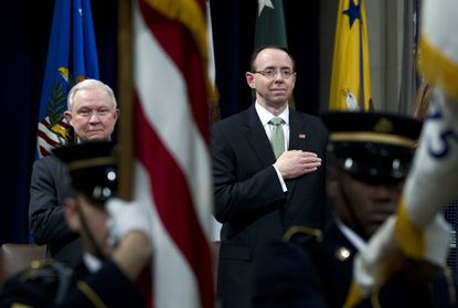 Attorney General Jeff Sessions accompanied by Deputy Attorney General Rod Rosenstein listen the national anthem during the opening ceremony of the summit on Efforts to Combat Human Trafficking at Department of Justice in Washington, Feb. 2, 2018. President Donald Trump refused to express confidence in Rosenstein as he approved release of a memo critical of the Department of Justice and FBI.