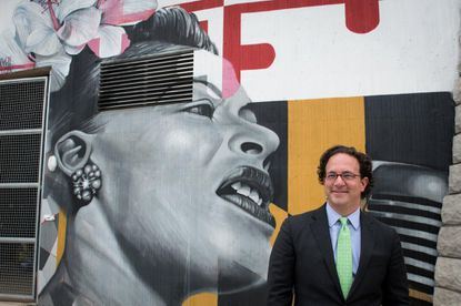 Toby Bozzuto, President and CEO of The Bozzuto Group, stands next to a mural of Billie Holiday, which is painted at The Anthem House, a new apartment complex in the Locust Point neighborhood in Baltimore.