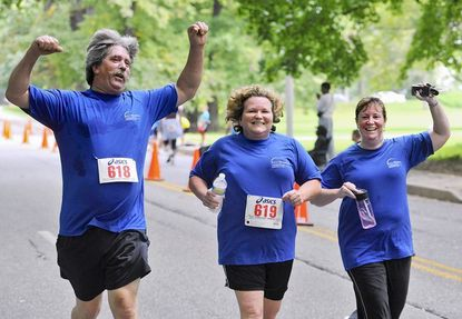 """Larry Sener, 56, left, his wife Jean Sener, 53, center, and Kerry Riggs, 38, right, celebrate as they near the finish for a 5K run in the 7th annual """"Race For Our Kids"""" to benefit The Children's Hopsital at Sinai. They were part of a 25 person team, the Therapy Trotters, who all work in Sinai's Outpatient Rehab Department."""