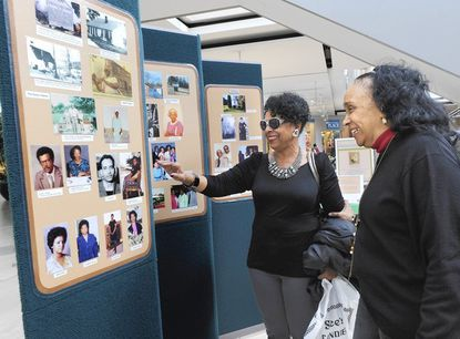Joan Smith Hash, left, shows her family's pictures to Janice Franklin a volunteer with the Howard County Center for African American Culture, Inc.(HCCAAC).