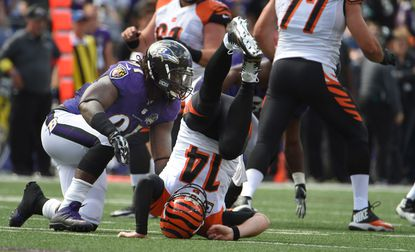 Cincinnati Bengals quarterback Andy Dalton throws a incomplete pass and is hit by Baltimore Ravens linebacker Courtney Upshaw in the second quarter at M&T Bank Stadium.