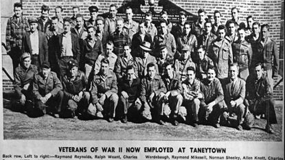 World War II veterans employed by the Cambridge Rubber Company in Taneytown pose in front of a WW II Honor Roll Memorial which can be seen in the background. The photo appeared in the company's newspaper, The Tattler. Date of the photo is not known.