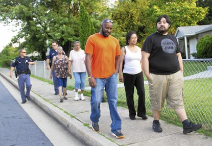 Residents of the Winters Lane community Sherlyon Brathwaite, 42, left, and Steven Trabbic, 26, right, walk next to each other as part of a National Night Out event held Tuesday by the Concerned Citizens of Catonsville to prevent crime.