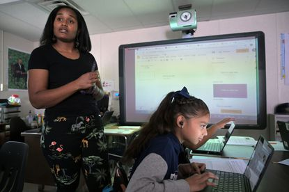 Holabird Academy sixth grader Angie Castro, 11, works on a project about who she feels deserves a monument while teacher Sidney Thomas gives additional instruction.