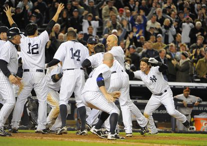 Yankees players celebrate after Raul Ibanez's walk-off home run in the 12th inning gave them a 3-2 win over the Orioles in Game 3 of the American League Division Series at Yankee Stadium.