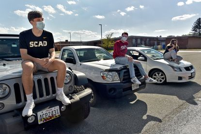 South Carroll High School seniors, from left, Ayden Behn, 17, Chase Cote, 18, and Abbie Shorter, 17, hang out together in the senior-designated parking lot at their school. Like all seniors, they are facing uncertain times during the pandemic, without the expected milestones of proms, senior week, and graduation ceremonies. May 13, 2020