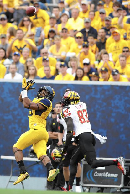 West Virginia cornerback Terrell Chestnut (16) intercepts a pass intended for Maryland wide receiver Malcolm Culmer (83) during the first half of an NCAA college football game, Saturday, Sept. 26, 2015, in Morgantown, W.Va. West Virginia defeated Maryland 45-6. (AP Photo/Raymond Thompson)