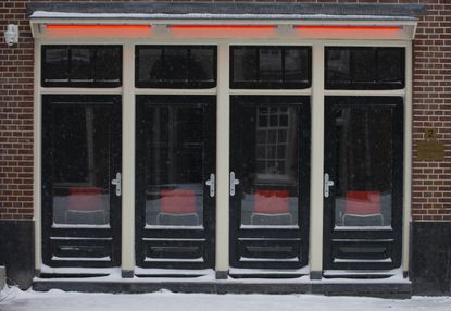 Four empty chairs of sex workers are seen in the capital's Red Light District, in Amsterdam, Sunday, Feb. 7, 2021. The Dutch government ordered them closed to curb the spread of the coronavirus during the COVID-19 pandemic. (AP Photo/Peter Dejong)