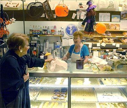 Customer Elly Wolff (left) laughs with Marge Hayes, behind the counter at Herman's Bakery, which has been a must stop for many visitors to the Shops at Kenilworth since the Towson shopping center opened in 1978.