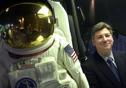 Gregory P. Andorfer, executive director of the Maryland Science Center, stands near a spacesuit in an exhibit on outer space.