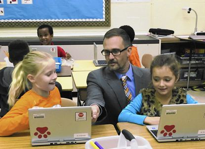 Baltimore County schools' digital leader Ryan Imbriale visits a classroom at Warren Elementary School on Oct. 30. New HP Revolves were being delivered to the school that day. At left is Imbriale's daughter, Hayden Imbriale and right, Macy Erdman.