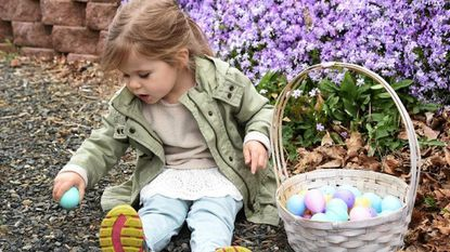 London Howard of Bel Air decides to use the ground to help open her plastic egg after having some trouble prying it open after the Easter Egg Hunt at Rockfield Manor in Bel Air at the 2018 egg hunt.