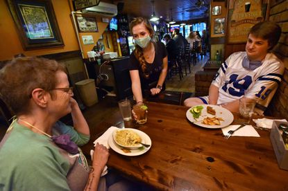 Miranda Sanders, center, waits on Mary Allan, left, and her son Colin Allan of Bel Air at Sean Bolan's Irish Pub in October. Sean Bolan's owner, Dave Brown, praised Gov. Larry Hogan's decision Thursday to rescind the order that restaurants must close by 10 p.m.