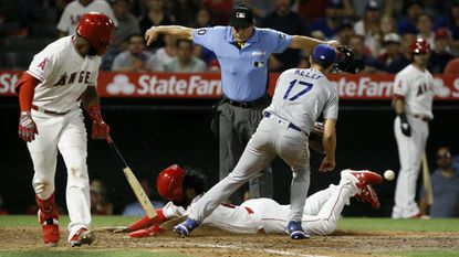Home plate umpire Phil Cuzzi makes the call as Angels' Brian Goodwin, center, scores on a wild pitch, as the throw back to Dodgers reliever Joe Kelly gets away and Angels' Luis Rengifo, left, gets out of the way.