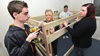 Karin DuBois, second from left, co-president of the Maryland chapter of Sleep in Heavenly Peace, her daughter, Kristyn Ferraro, who is also co-president, and volunteers Robert Reed, 17, left, and his father, Rich Reed, bring two sets of bunk beds to an Aberdeen family.
