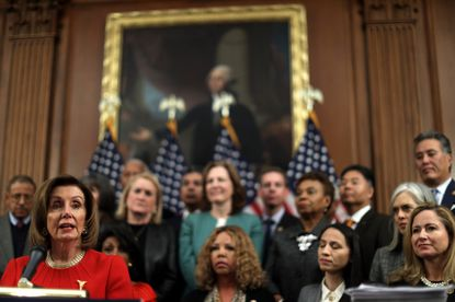 """Speaker of the House Rep. Nancy Pelosi speaks as other House Democrats look on during an event at the Rayburn Room of the U.S. Capitol December 19, 2019. House Democrats held an event celebrating the """"legislative progress the House Democratic Majority has made For The People in 2019."""