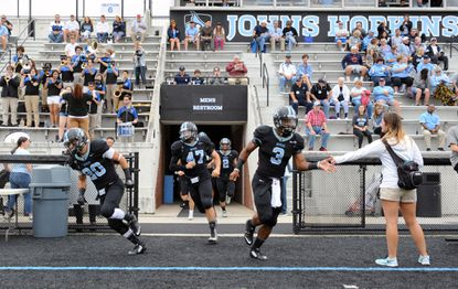 Johns Hopkins football players Dan Johnson (#20), Rob Gorman (#47) Stuart Walters (#3) and others run onto the field before game. Johns Hopkins football, a Top 10 and perennial playoff team, defeated the Muhlenberg Mules by score of 49 to 28 at Homewood Field.