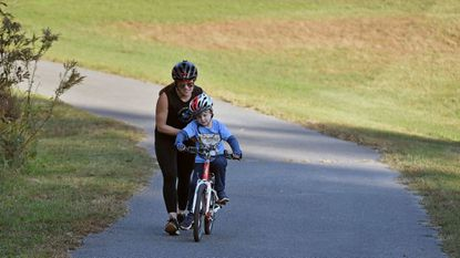 Rachel Varn helps Ben Waters, 6, navigate a hill at Kinder Farm Park. Varn, owner of PedalPower Kids, teaches children bike-riding skills and safety.