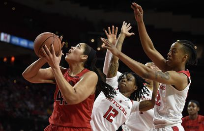 Maryland's Brionna Jones, left, shoots as Rutgers' Khadaizha Sanders, center, and Kandiss Barber defend during the first half.