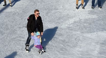 Stewart Becker of Locust Point, steadies his 4-year-old daughter, Helena as they take to the kice at the Inner Harbor rink Friday.