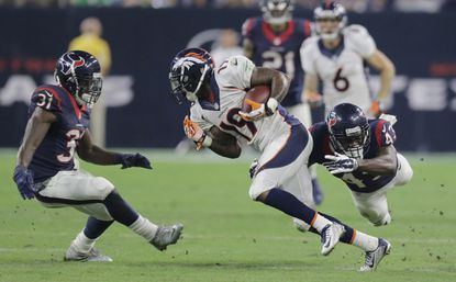 The Denver Broncos' Isaiah Burse is pursued by the Houston Texans' Charles James (31) and Corey Moore (43) during the second half of a preseason game.
