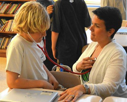 Kate Sturiano, a nurse practioner, shows third-grader Will Ohnmacht how to listen to the heart using a stethoscope during Rodgers Forge Elementary School's Career Day.