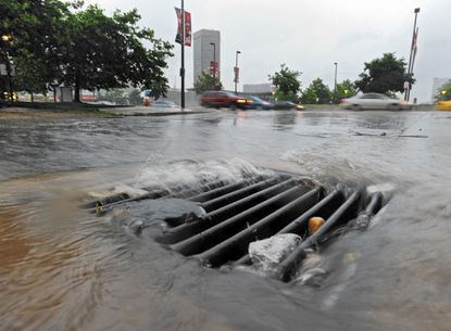 Rain water rushes into a storm drain as a severe thunderstorm passed through Baltimore. Baltimore County will again be selling rain barrells to capture such downpours for residents' future use in their gardens and lawns.