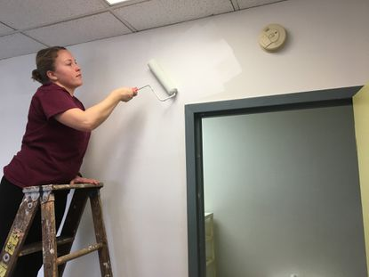 Allison Hoffman paints a resident's room at Project PLASE homeless shelter as part of Martin Luther King, Jr. Day of Service Monday.