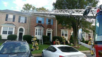 Firefighters control a townhouse fire on Ferring Court in Abingdon Friday afternoon. Investigators say an operating sprinkler system minimized damage.