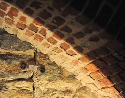 Cracks from the August 2011 earthquake spread in the basement of the Baltimore Basilica, six years after a $40 million restoration of the oldest Catholic cathedral in the nation. A device monitors structural shifts.